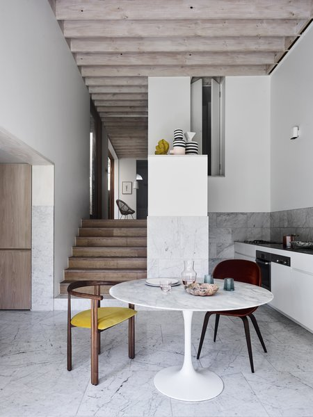The ground floor steps down to the kitchen and sunken lounge at the rear, and an exposed timber ceiling adds texture and rhythm to the interior.