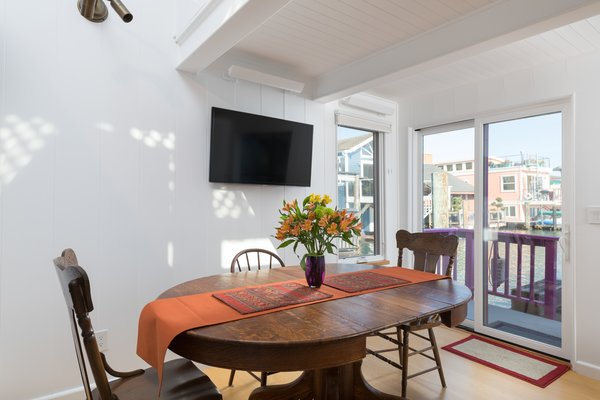 Sliding glass doors in the dining area offer direct outdoor access while framing harbor views.